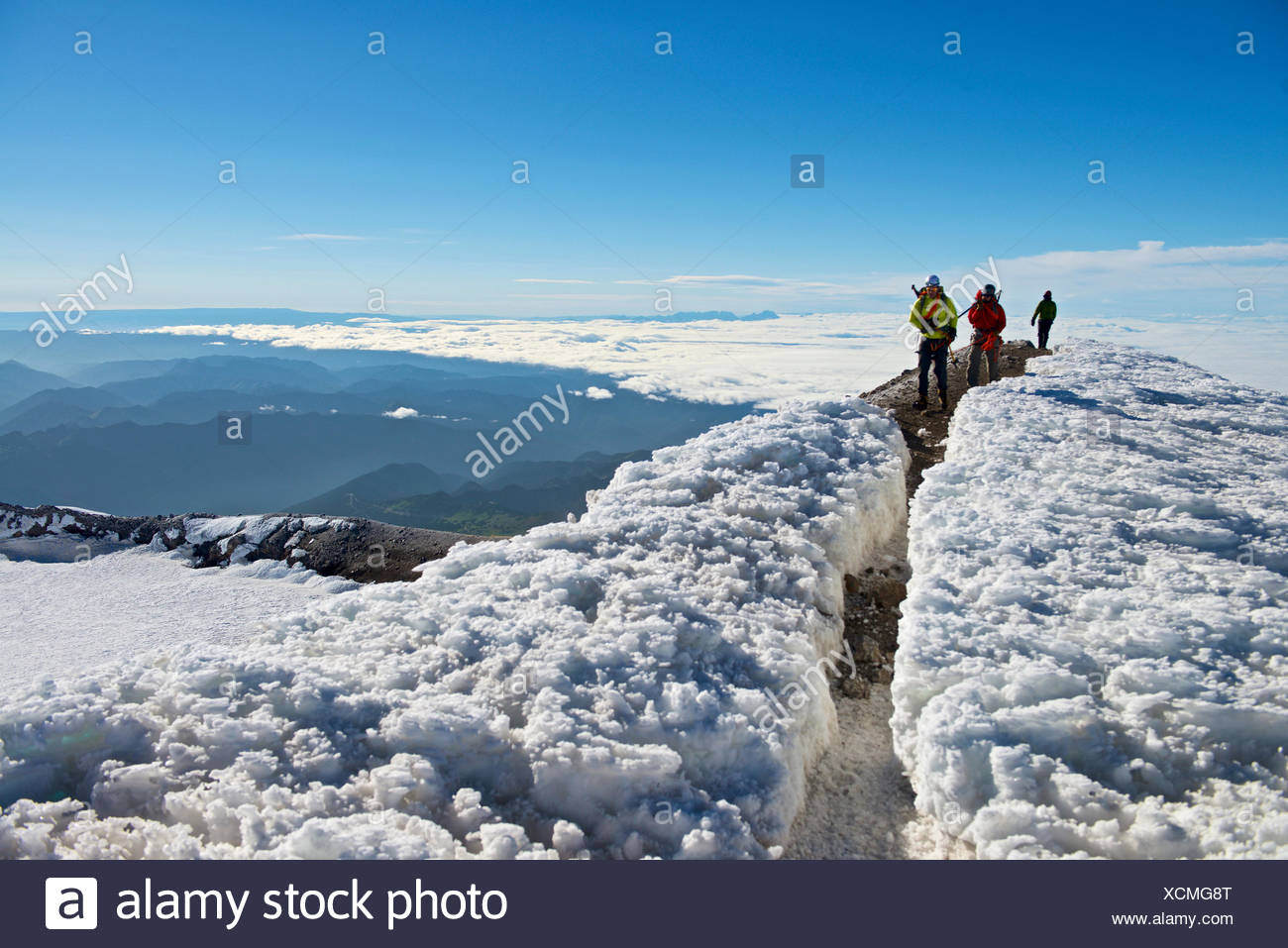 Group of three mountain climbers on Liberty Cap at summit of Mount Rainier,Mount Rainier National Park,Washington State,USA - Stock Image
