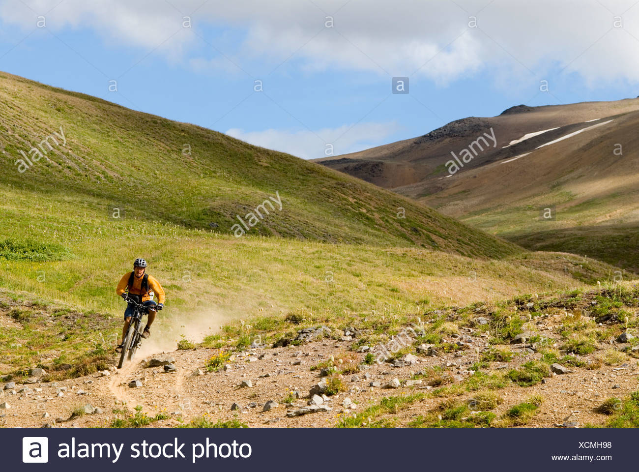 Mountain biker rides the trail down from Deer Pass, Southern Chilcotin Mountains, British Columbia, Canada. Stock Photo