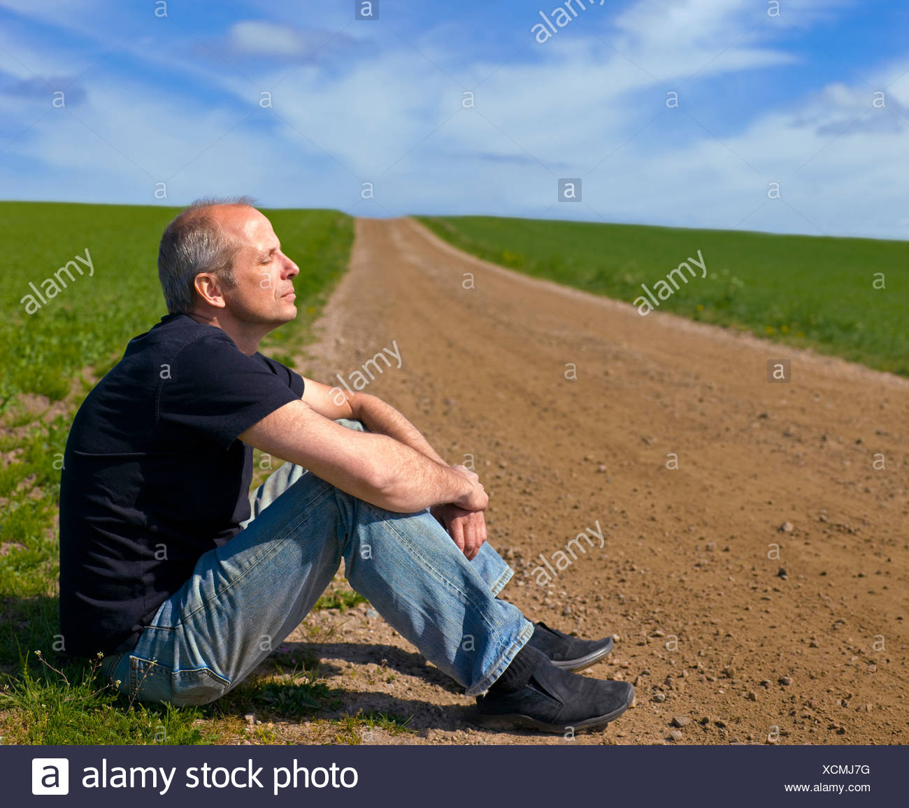 Side view of a mid adult man in casuals on the dirt country road along landscape - Stock Image
