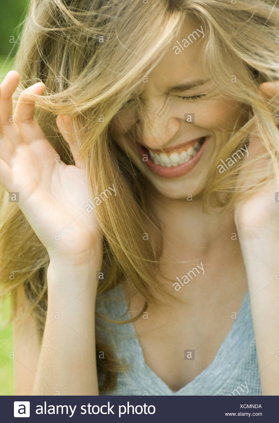 Young woman lowering head, shutting eyes and laughing with hands up - Stock Image