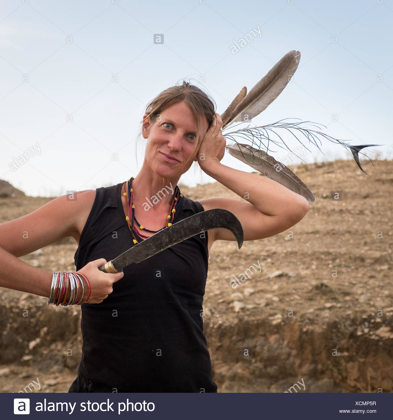 A German woman plays with feathers in her hair. - Stock Image