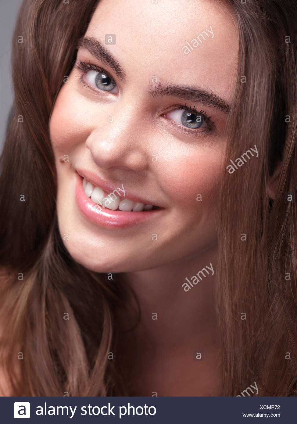 Smiling Woman With Long Hair And Bushy Eyebrows Stock Photo
