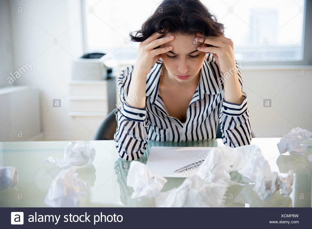 Overworked businesswoman sitting at desk - Stock Image