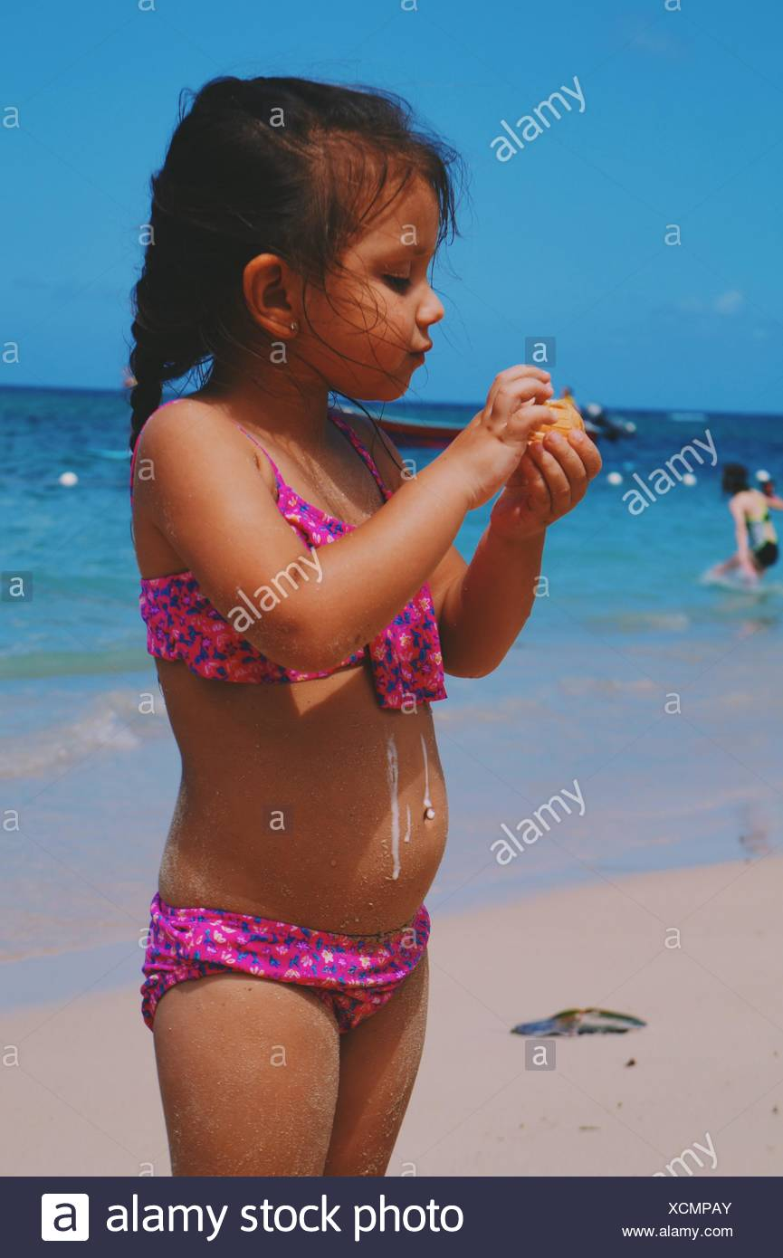 Cute Girl In Swimwear On Beach With Melting Ice Cream - Stock Image