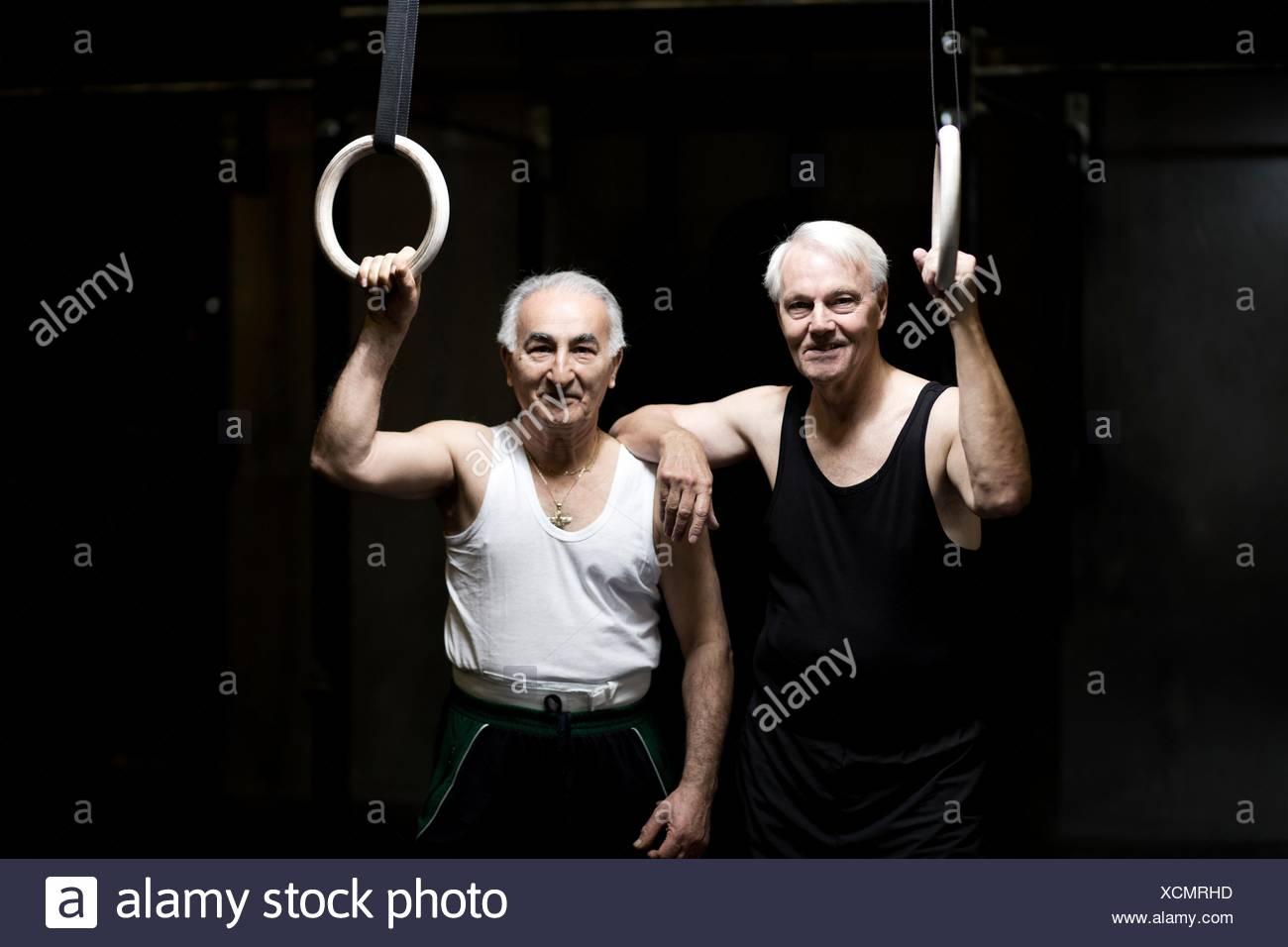 Portrait of two senior men holding gym rings in dark gym - Stock Image