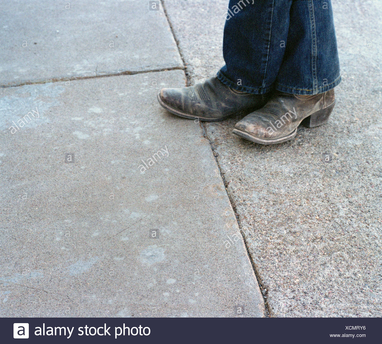 Close up of weathered cowboy boots and denim jeans - Stock Image