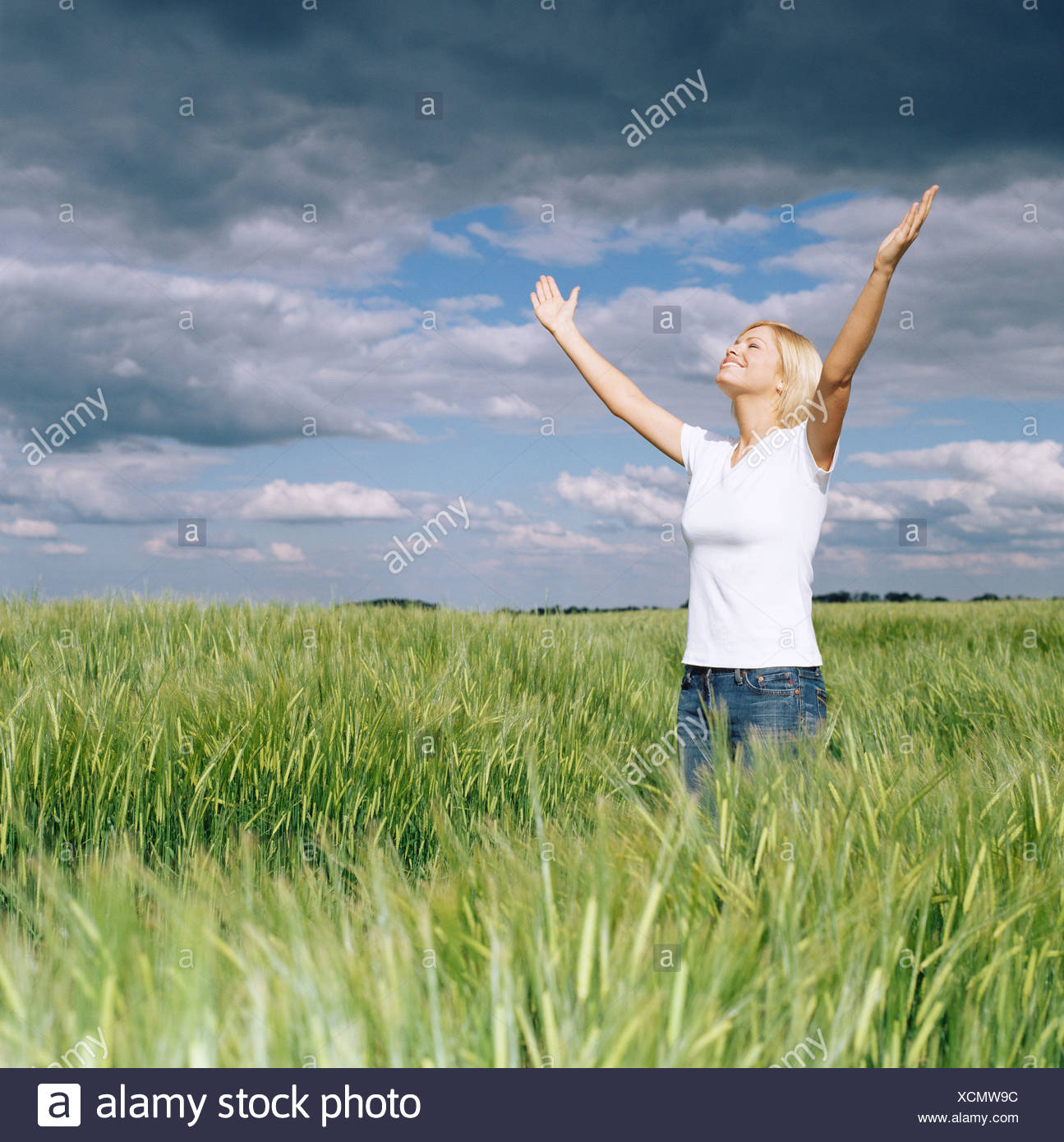 Woman with open arms in field Stock Photo