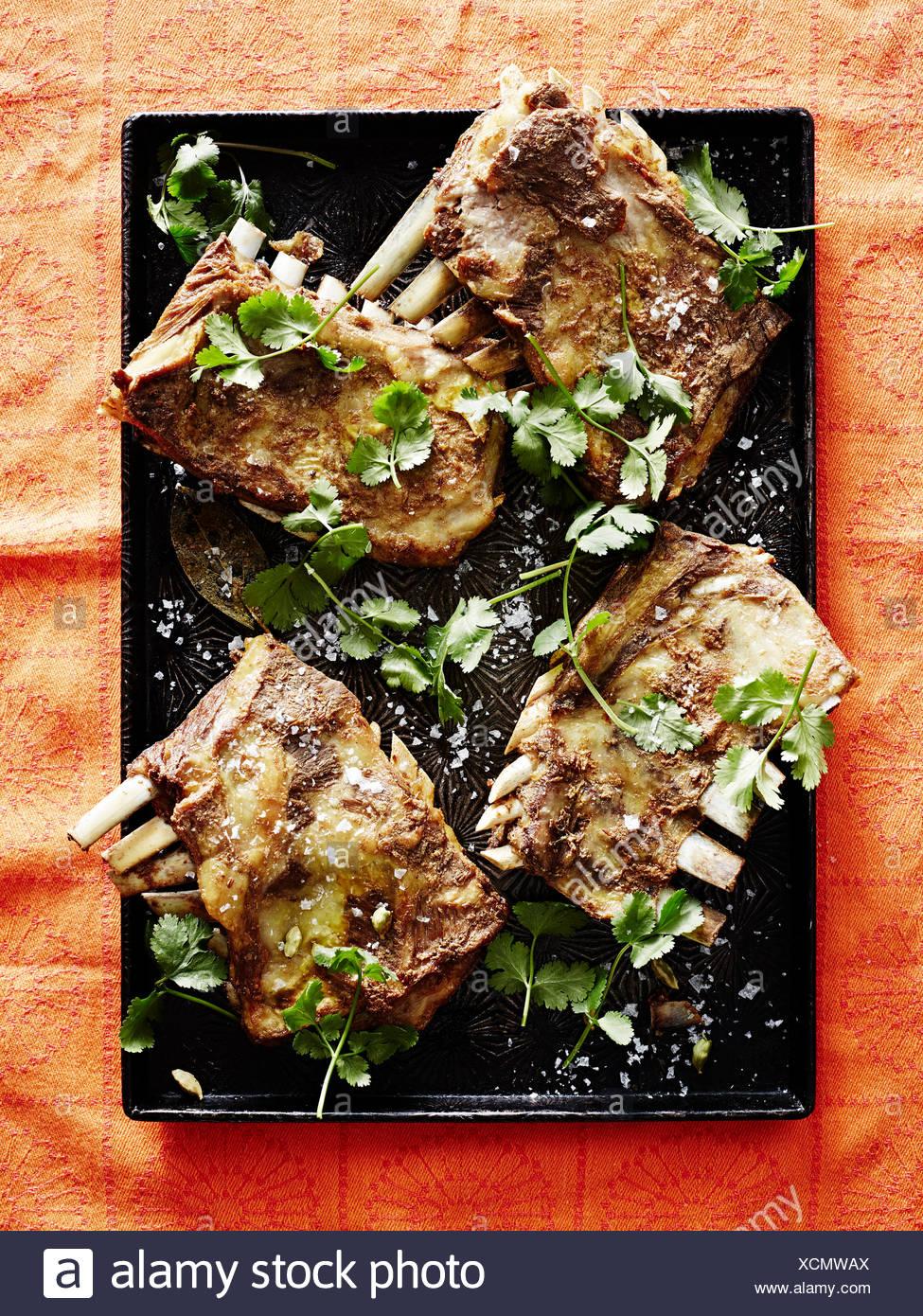 Roasting tin of Kashmiri tabak maaz (lamb ribs) - Stock Image