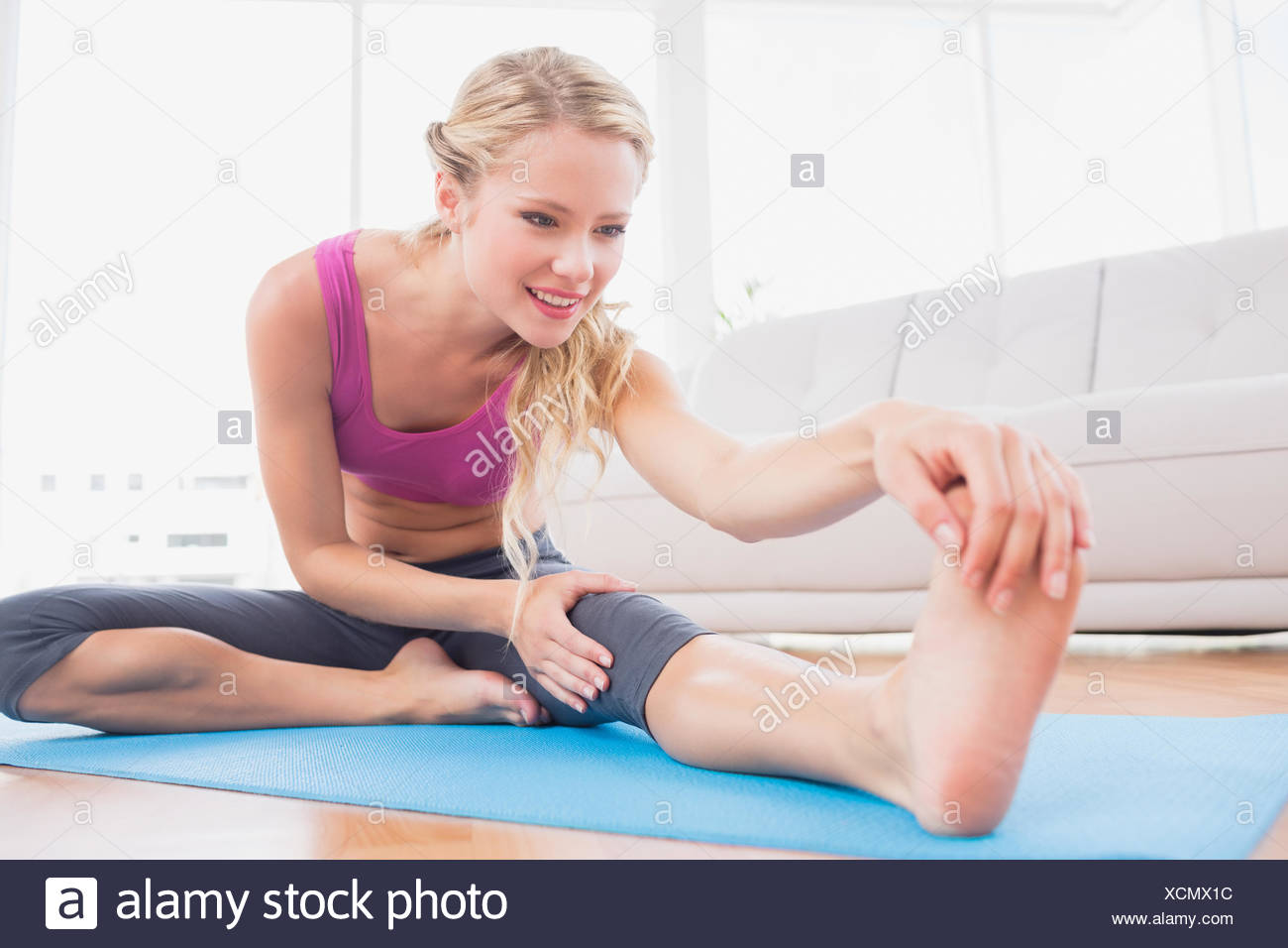 Toned blonde stretching on exercise mat - Stock Image
