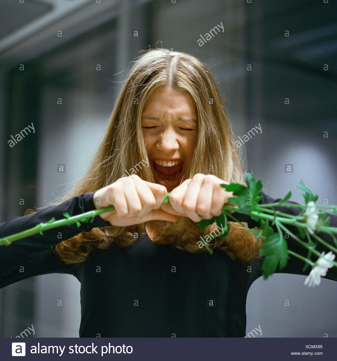 Woman holding out flowers, screaming - Stock Image