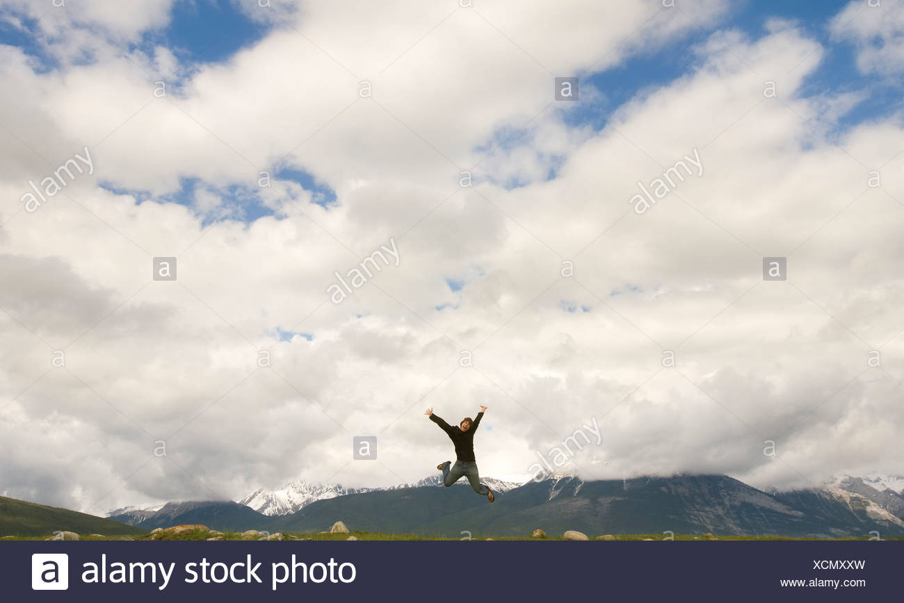 Person leaping on top of a mountain - Stock Image
