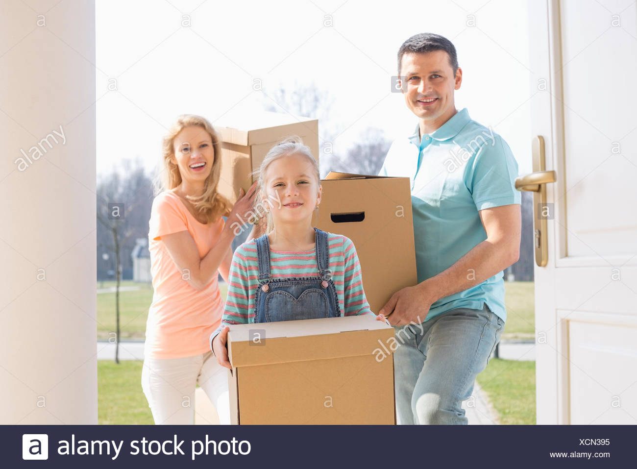 Happy family with cardboard boxes entering new home Stock Photo