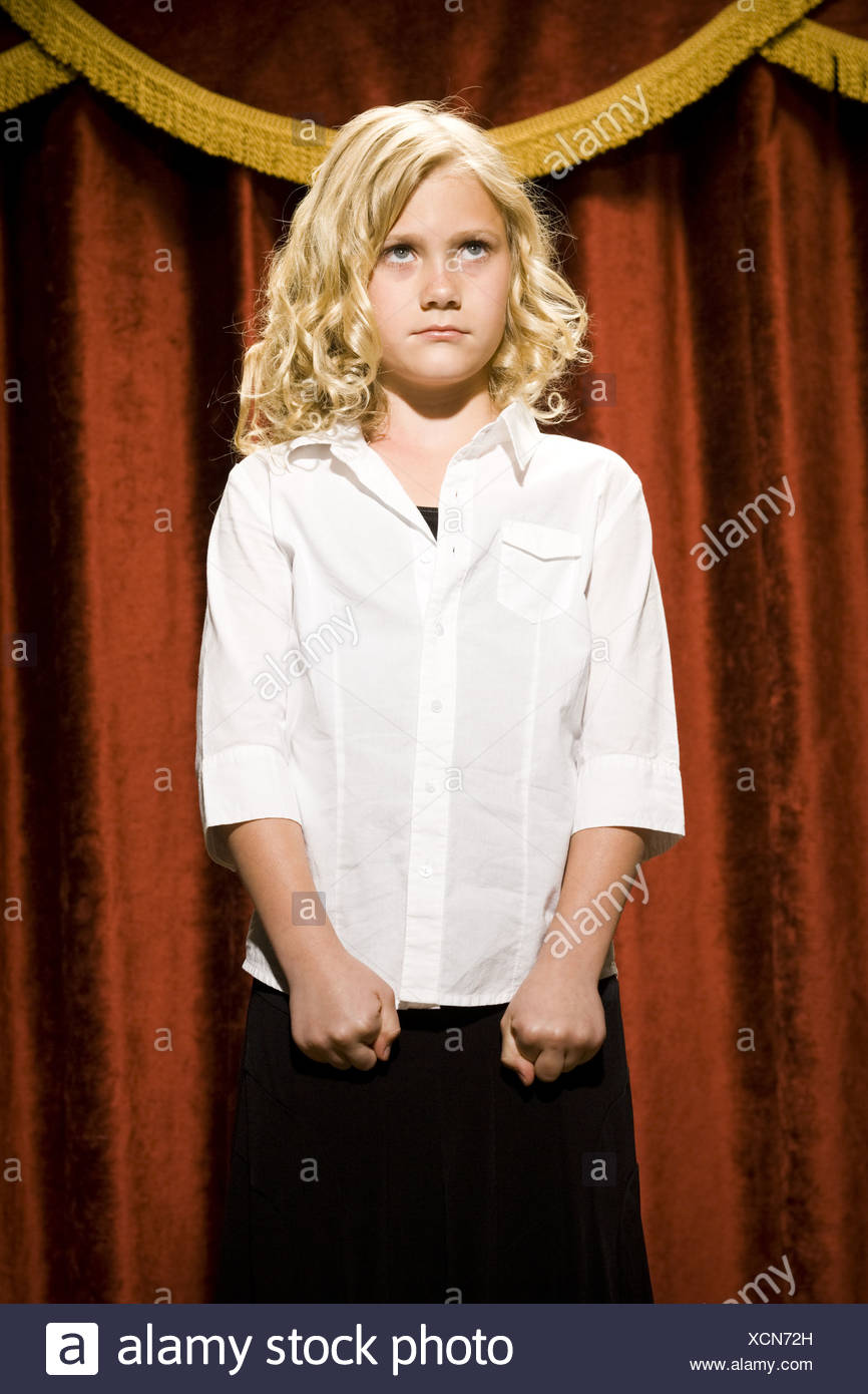 Girl standing on stage with lips pressed together - Stock Image