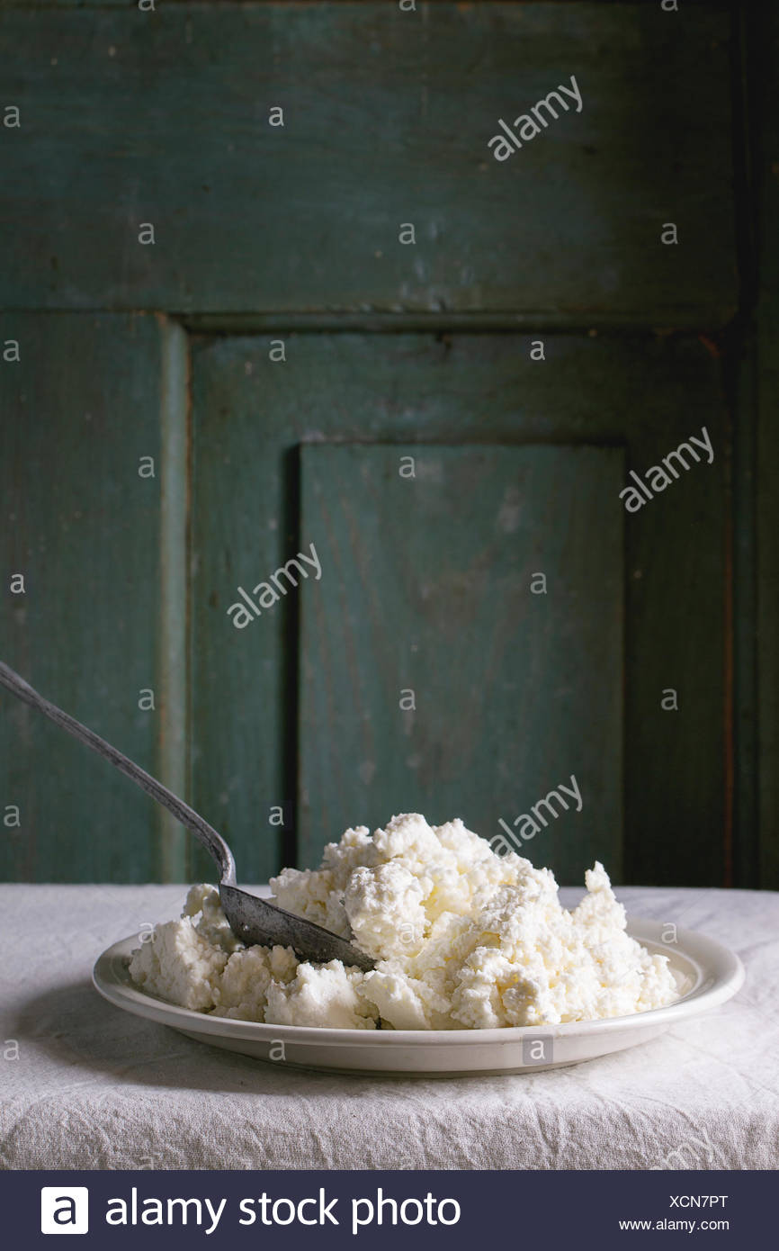 Plate of homemade cottage cheese on white tablecloth with turquoise wooden background. Dark rustic atmosphere. - Stock Image