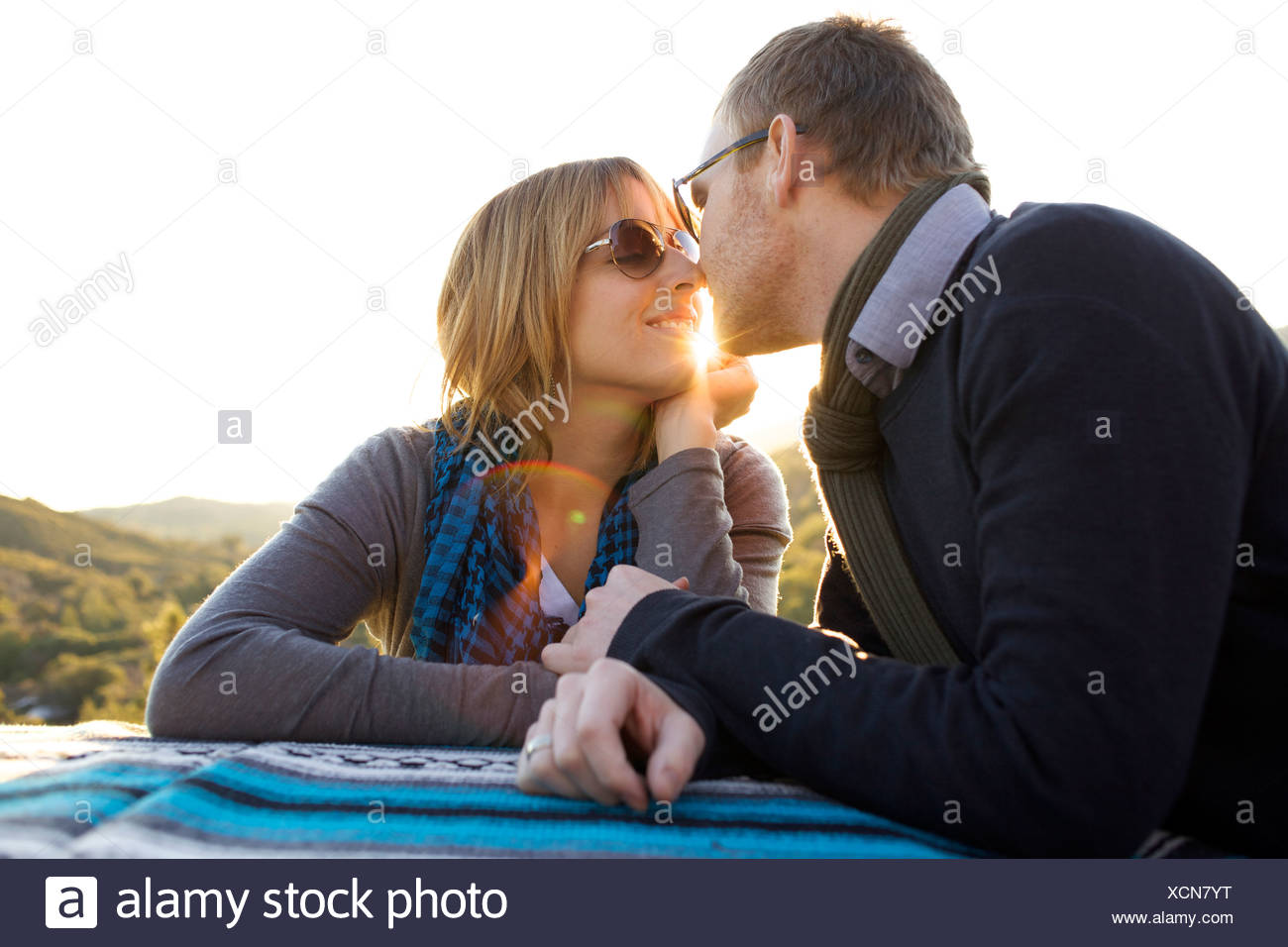 Couple approach each other to kiss on the side of the road. - Stock Image