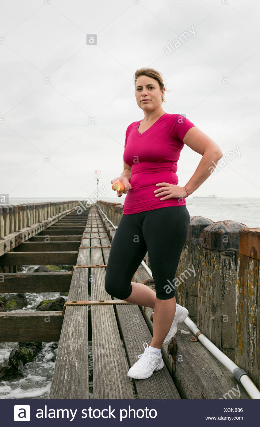 Woman standing on pier wearing sports clothing Stock Photo