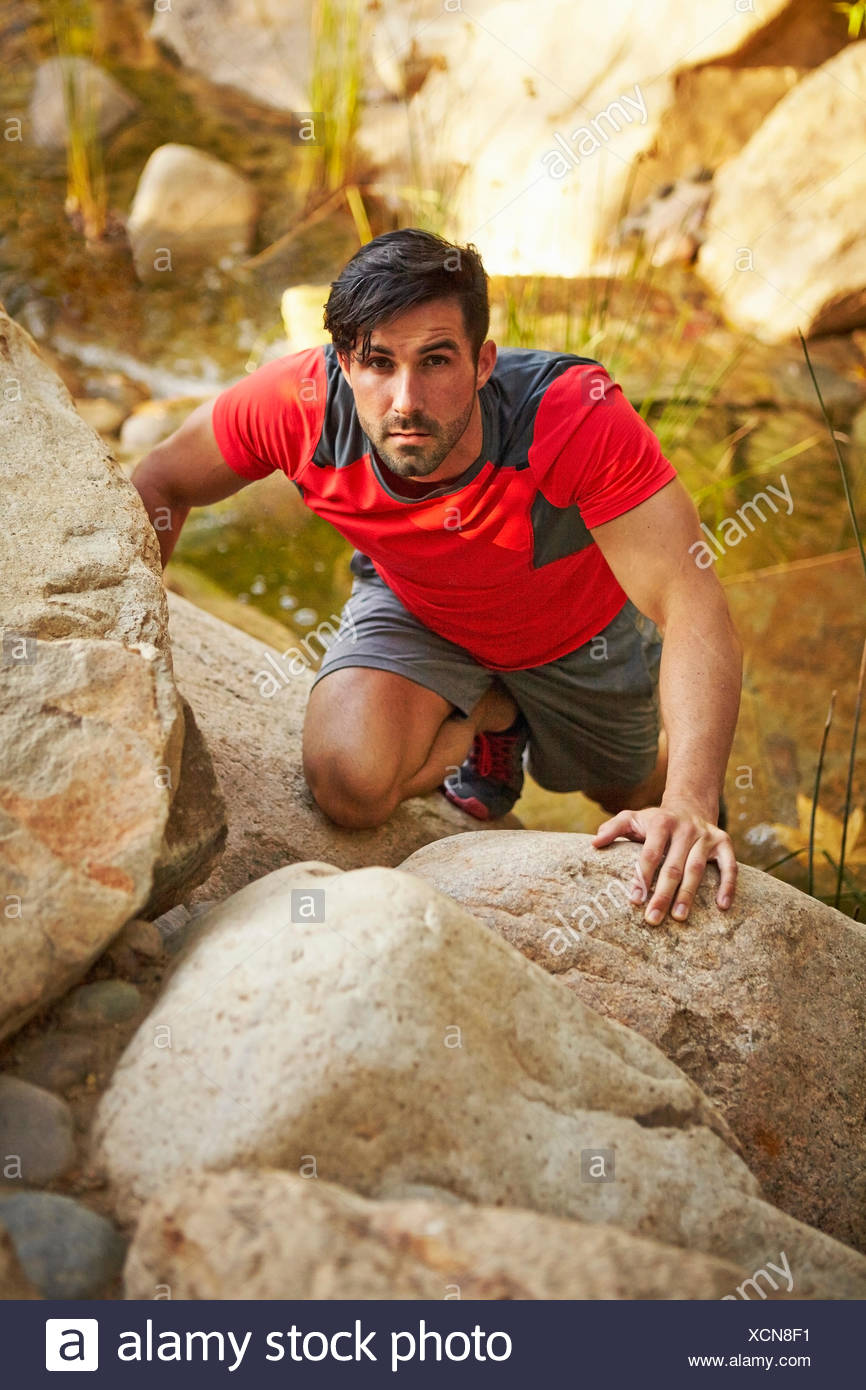 Young male free climber, climbing up rocks - Stock Image