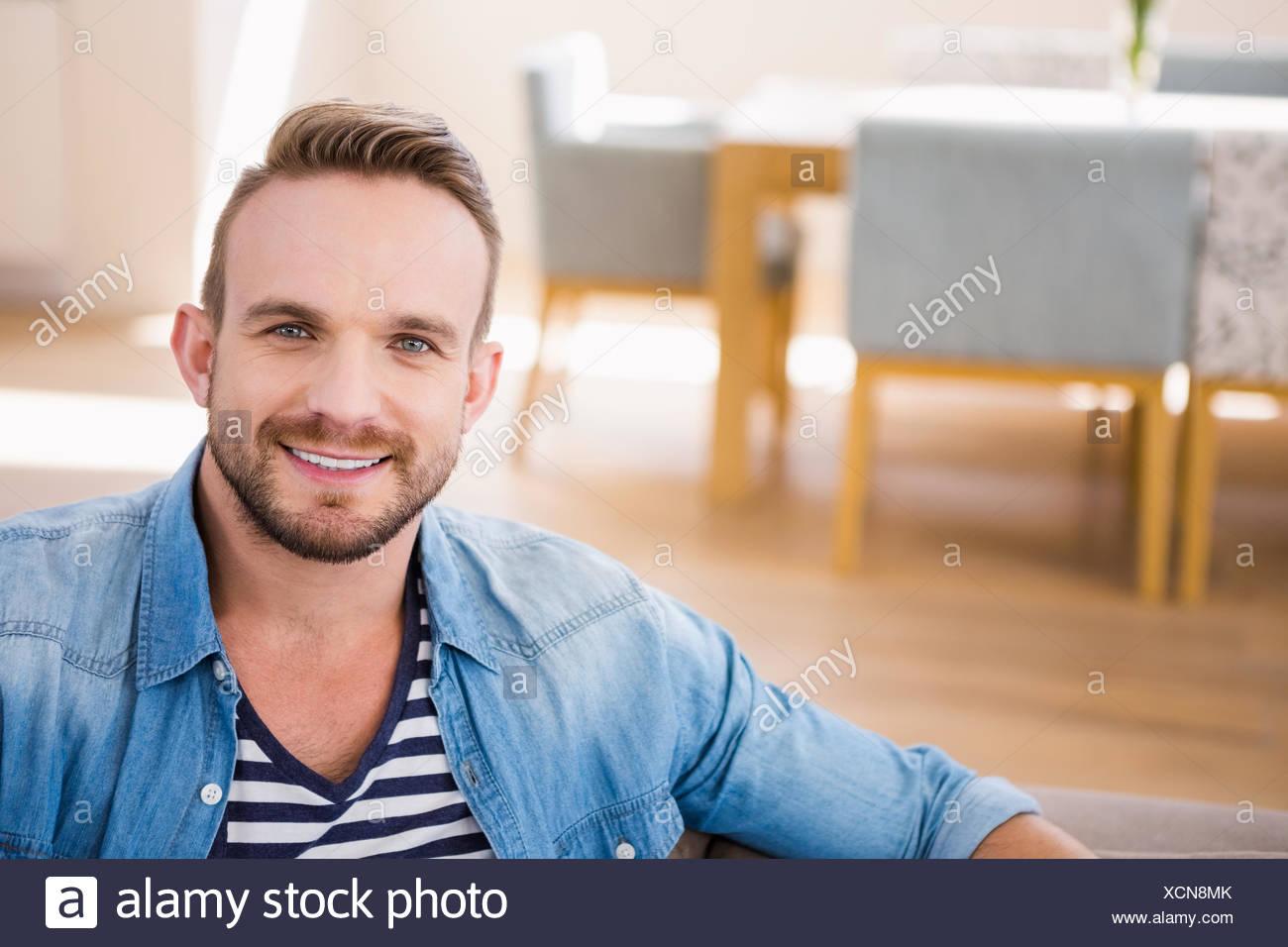 Handsome man smiling at camera - Stock Image
