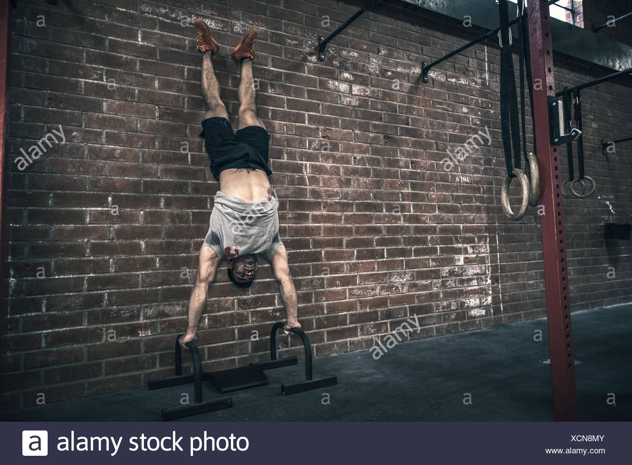 Young man doing handstand  in gym - Stock Image