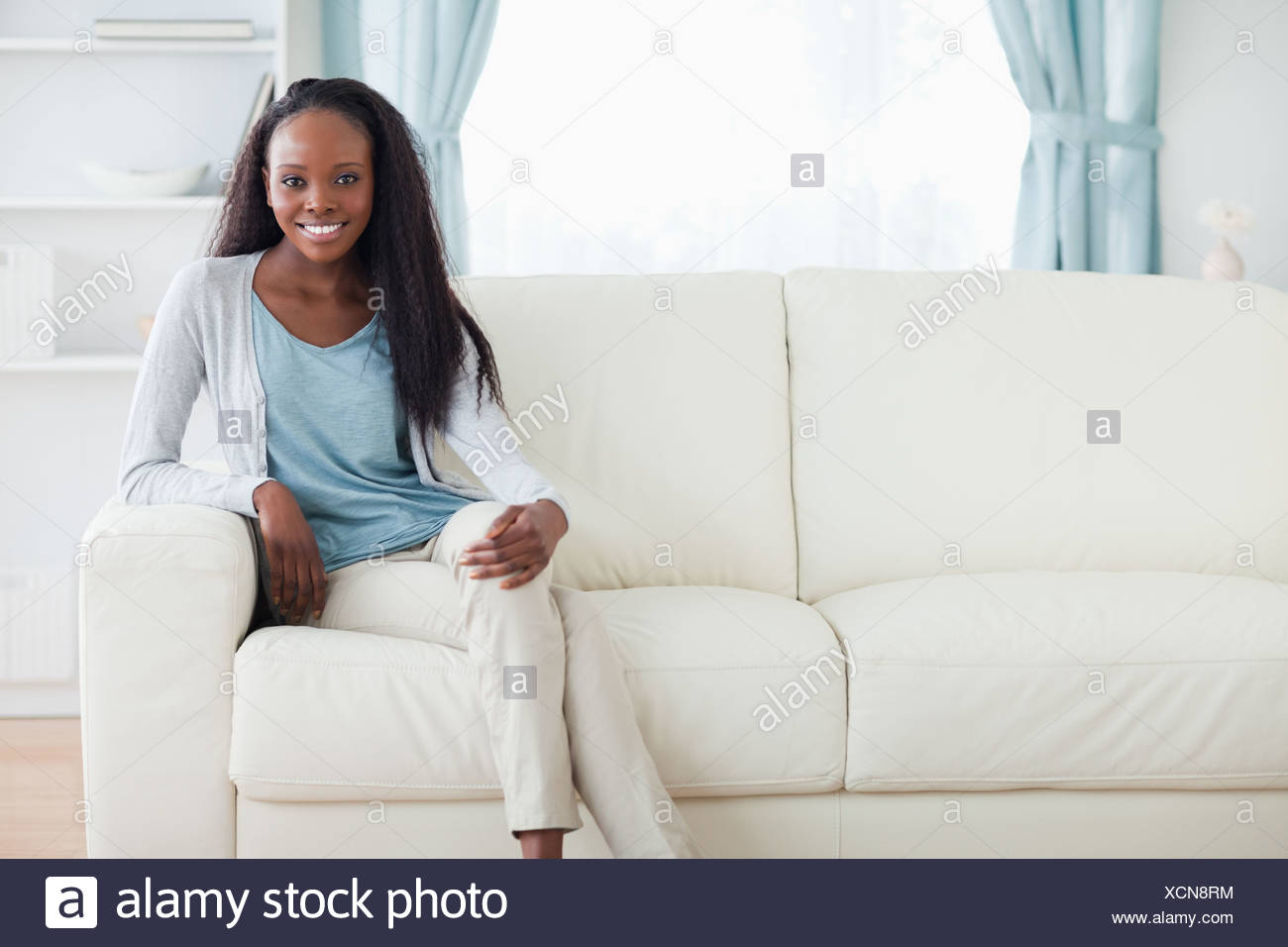Woman sitting on sofa with legs crossed Stock Photo