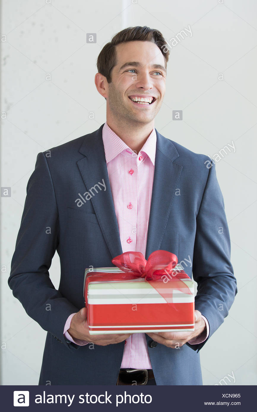 Well-dressed man with Christmas gift - Stock Image