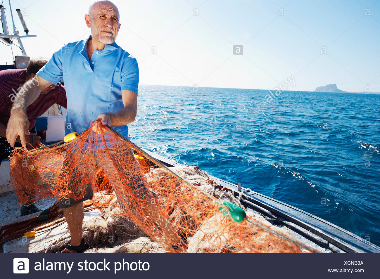 Fisherman on boat pulling in nets - Stock Image