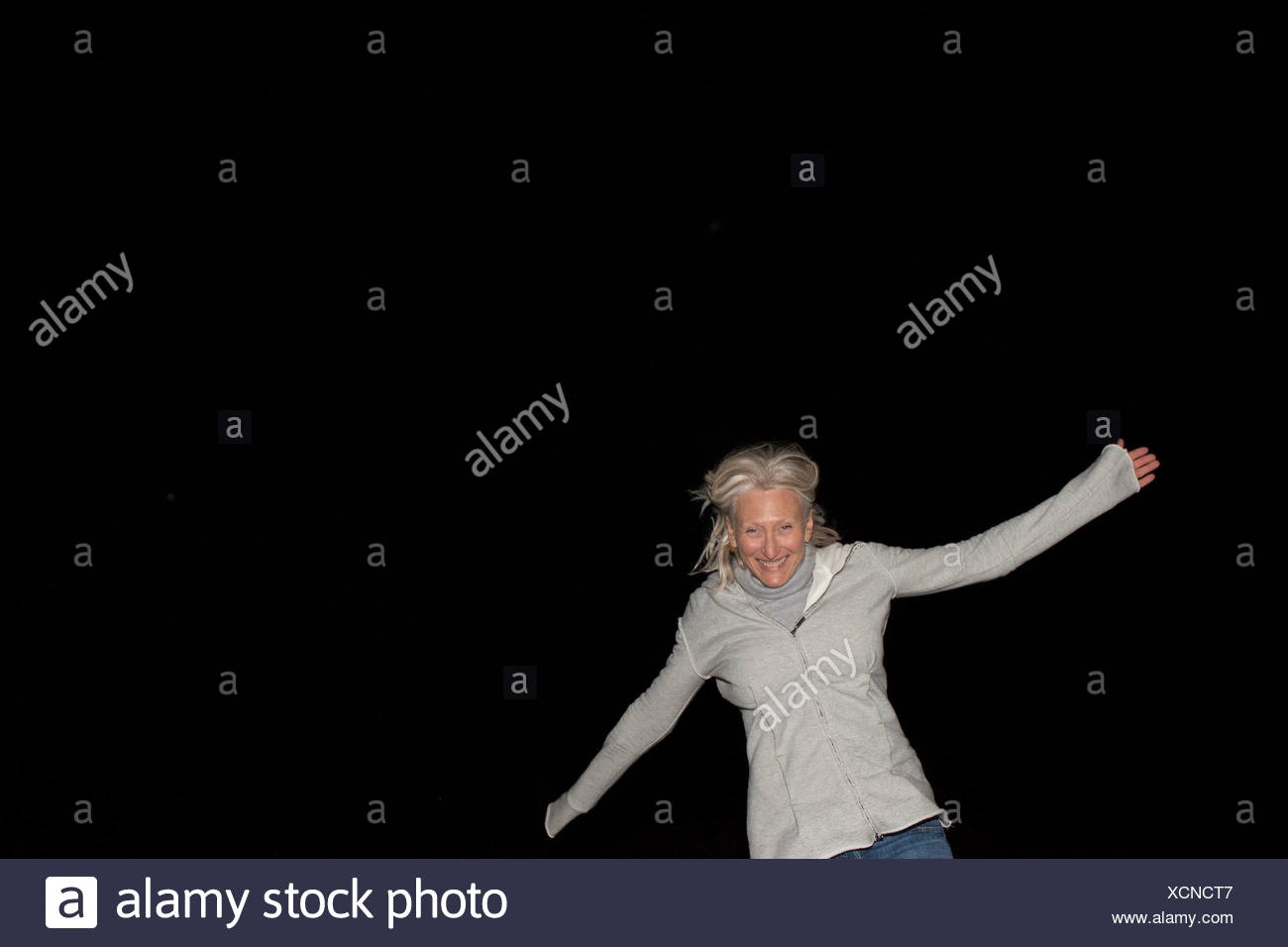 Portrait of mature woman with arms out at night - Stock Image