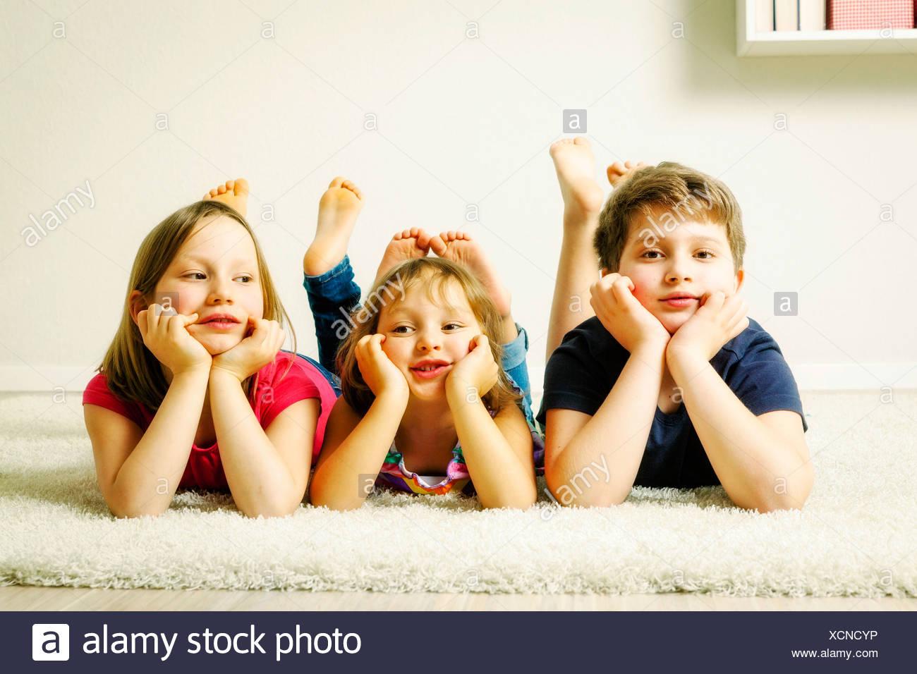 Three children relaxing hand on chin, Munich, Bavaria, Germany - Stock Image