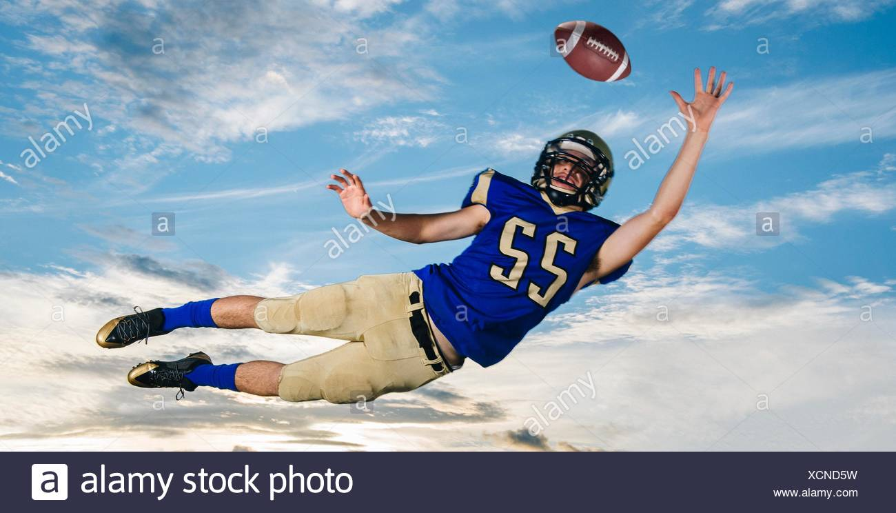 Male teenage American football player reaching to catch ball mid air against blue sky - Stock Image