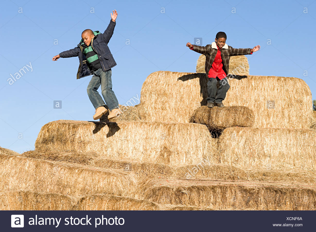 Boys jumping off bales of hay - Stock Image