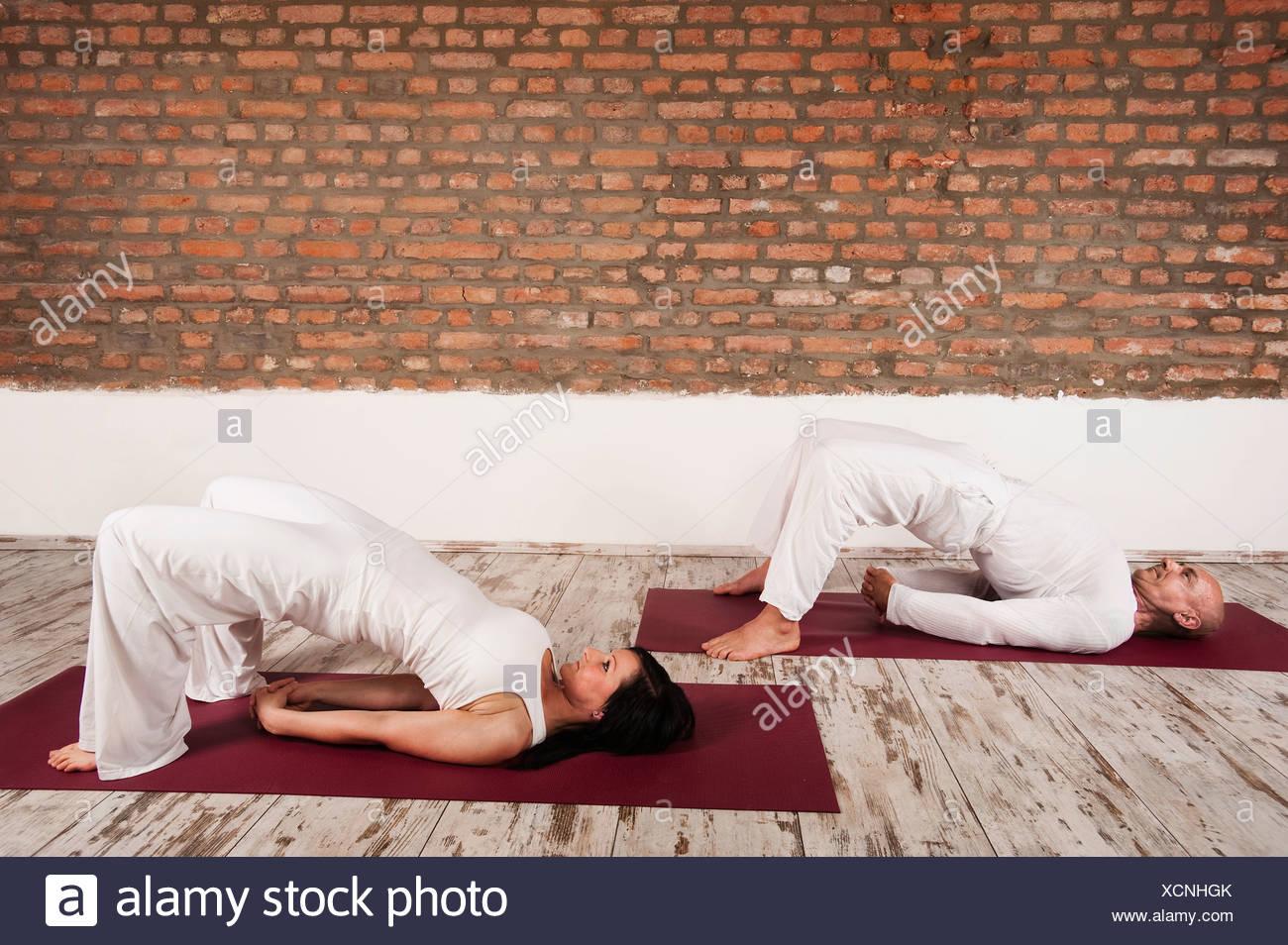Couple Practising Yoga, Bridge Pose - Stock Image