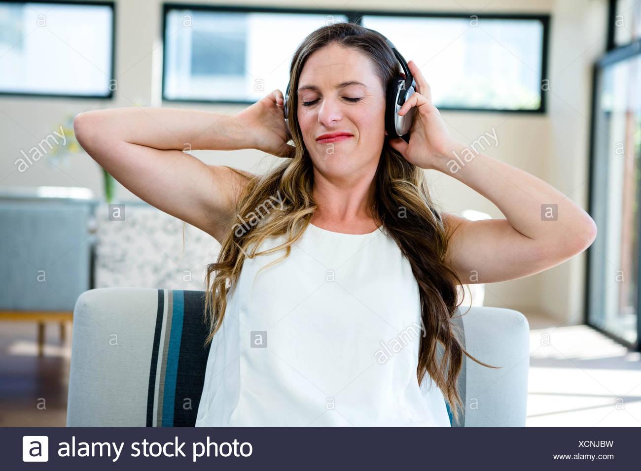 woman grimacing listening to headphone - Stock Image