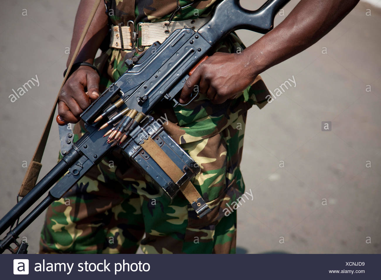 machine gun hanging over a soldier's shoulder during an event at the Independence Day (Juli 1), Burundi, Bujumbura Marie, Bujumbura - Stock Image