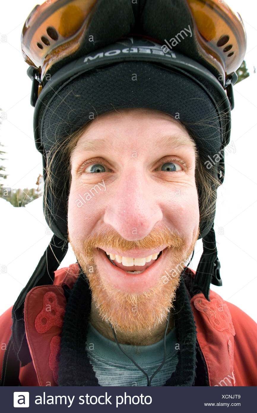 Man poses for a goofy portrait after skiing. - Stock Image