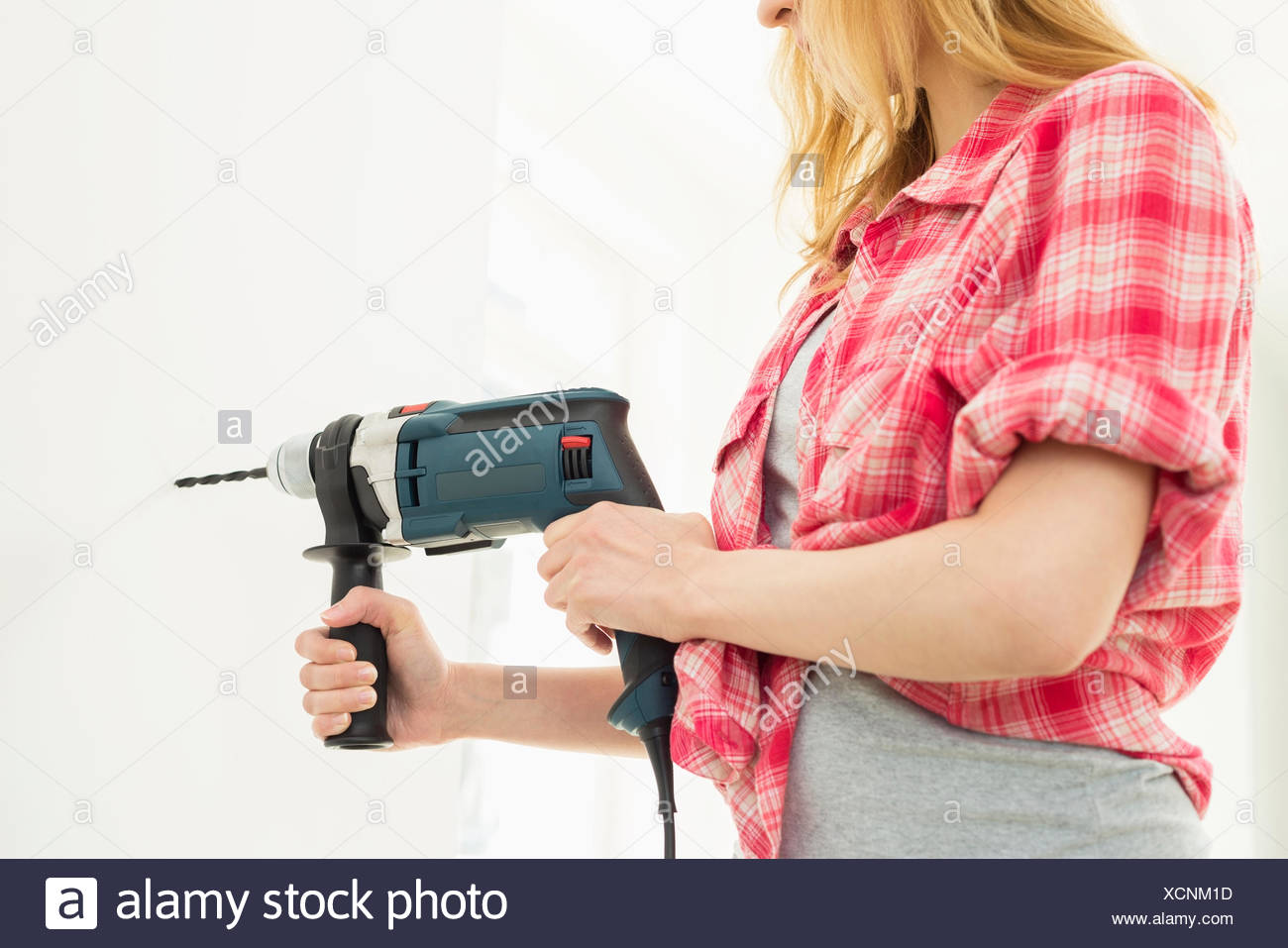 Midsection of woman drilling wall in new house - Stock Image