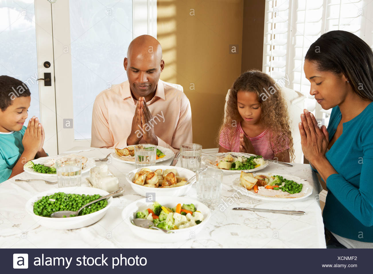 Family Saying Grace Before Meal At Home - Stock Image