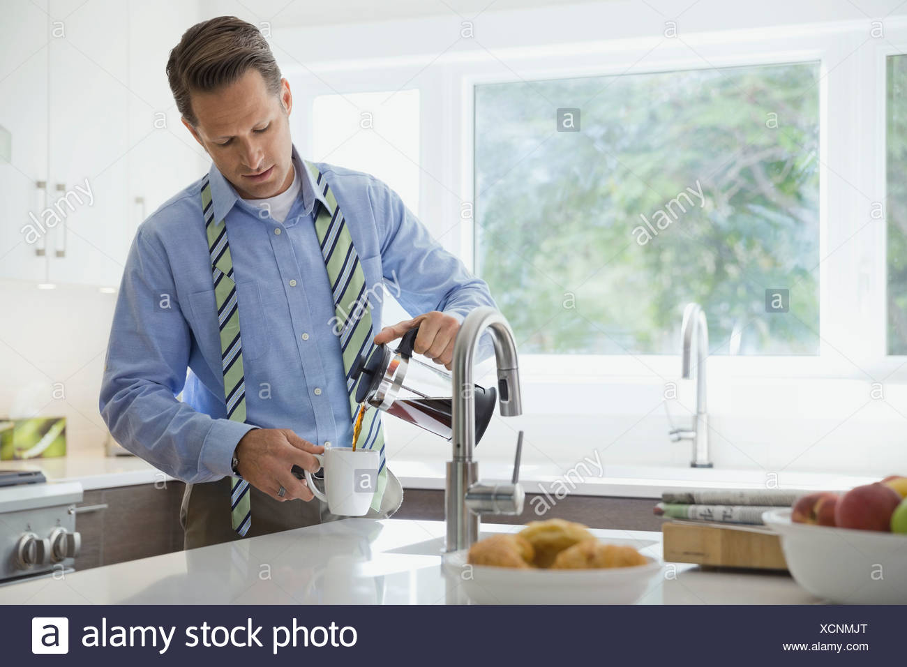 Businessman pouring coffee in domestic kitchen - Stock Image