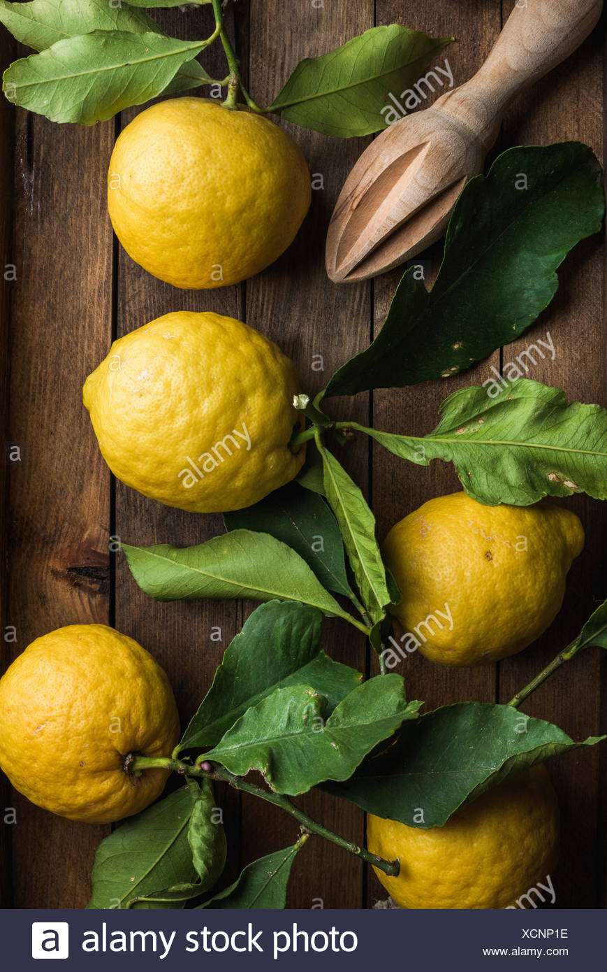 Fresh lemons with leaves in rustic wooden box. Top view - Stock Image