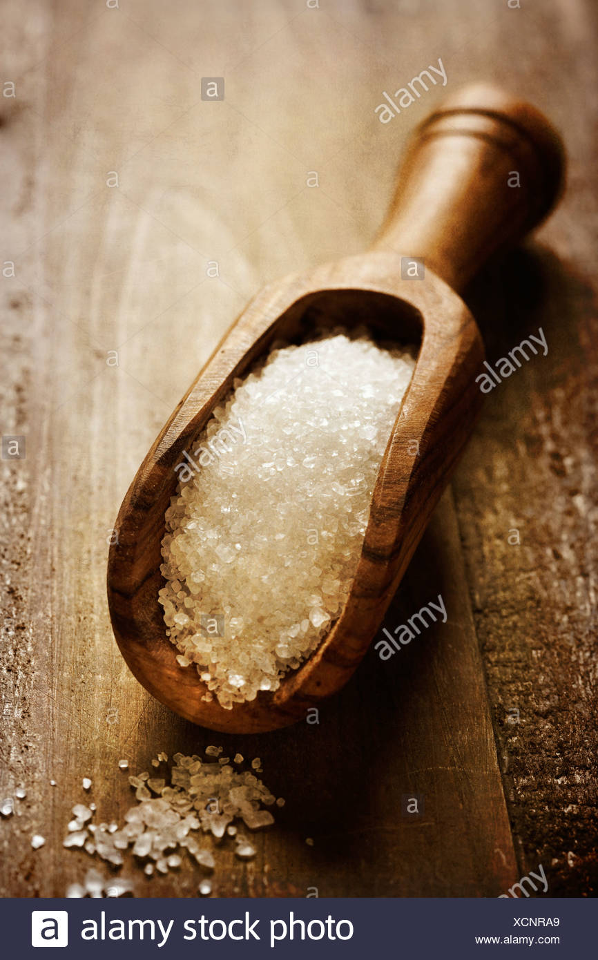 salt poured from wooden scoop on table - Stock Image