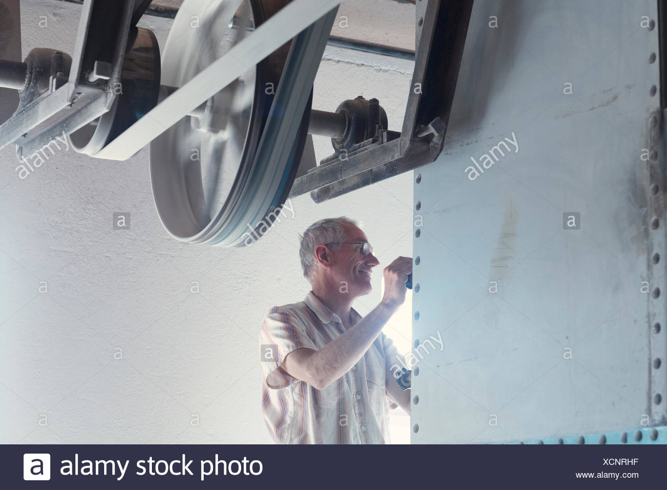 Male miller operating machine in wheat mill - Stock Image