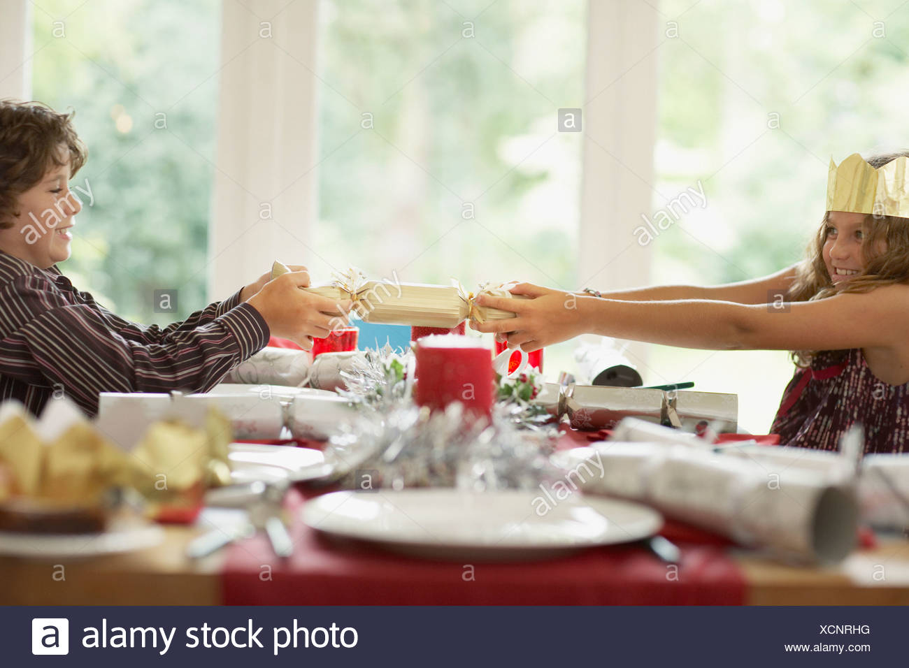 Brother and sister tugging Christmas cracker - Stock Image