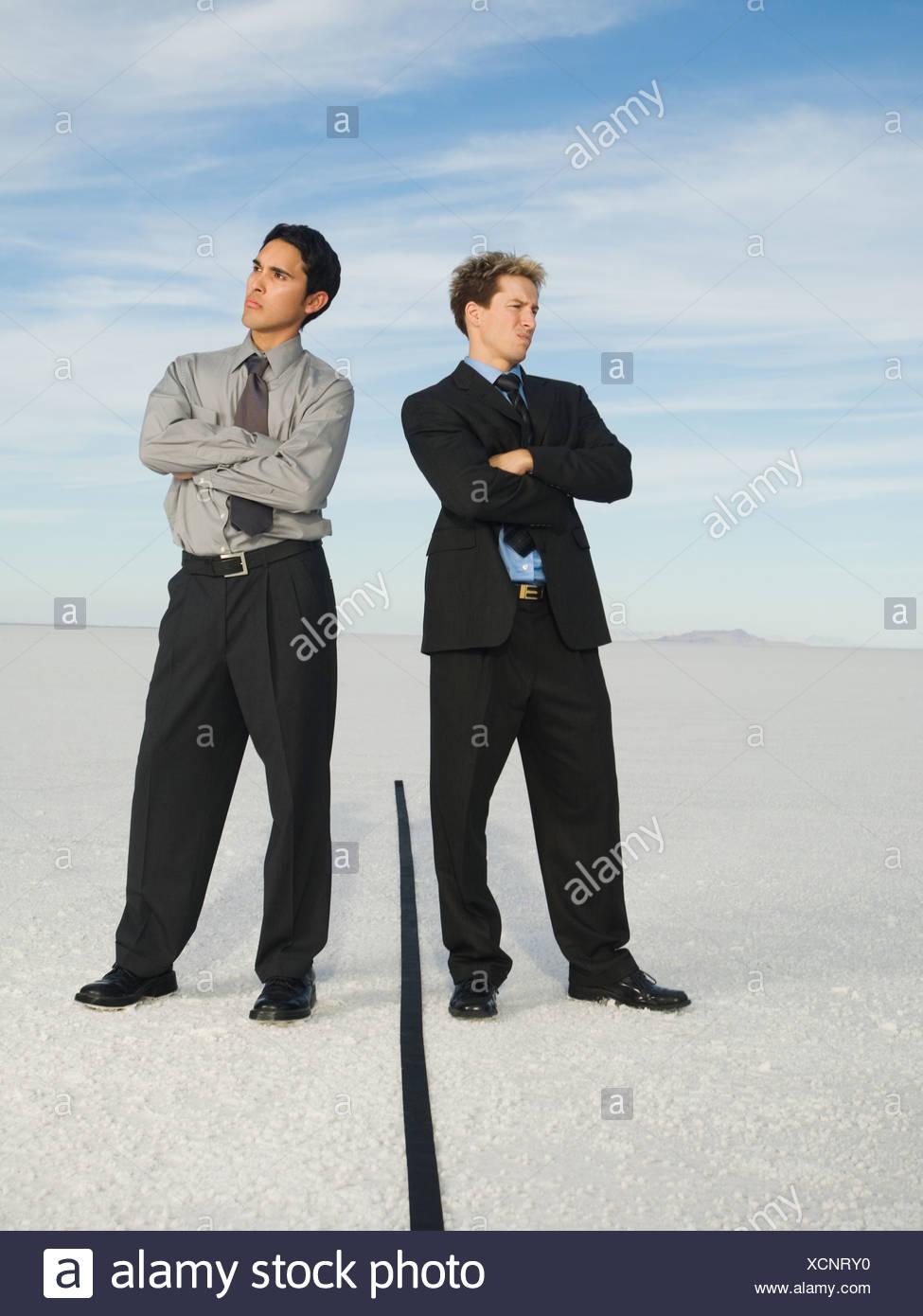 Businessmen on opposite sides of line, Salt Flats, Utah, United States - Stock Image