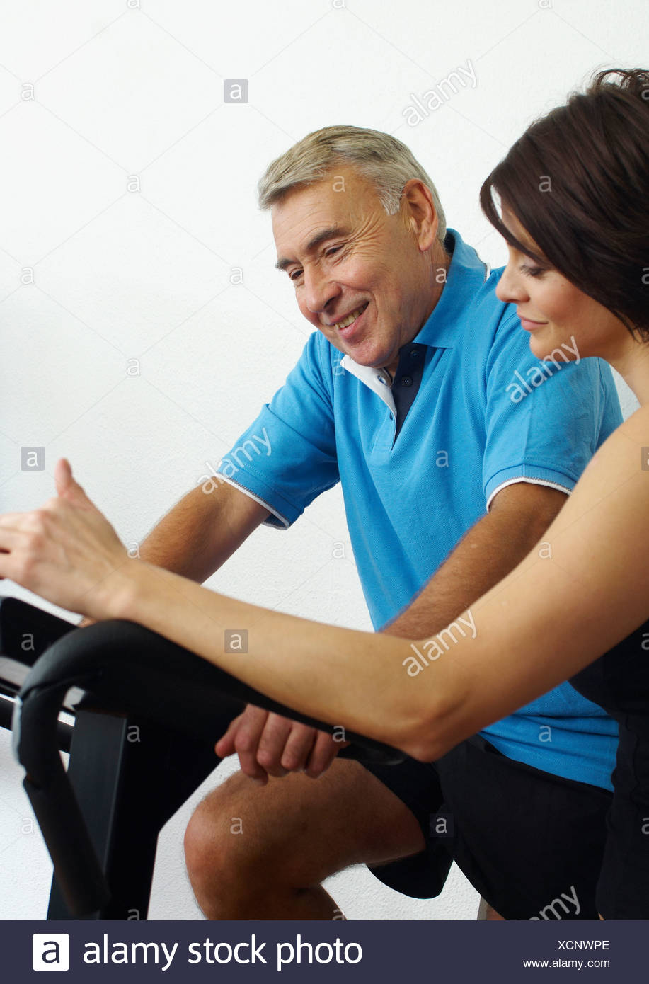 Woman and man in gym on exercise machines - Stock Image