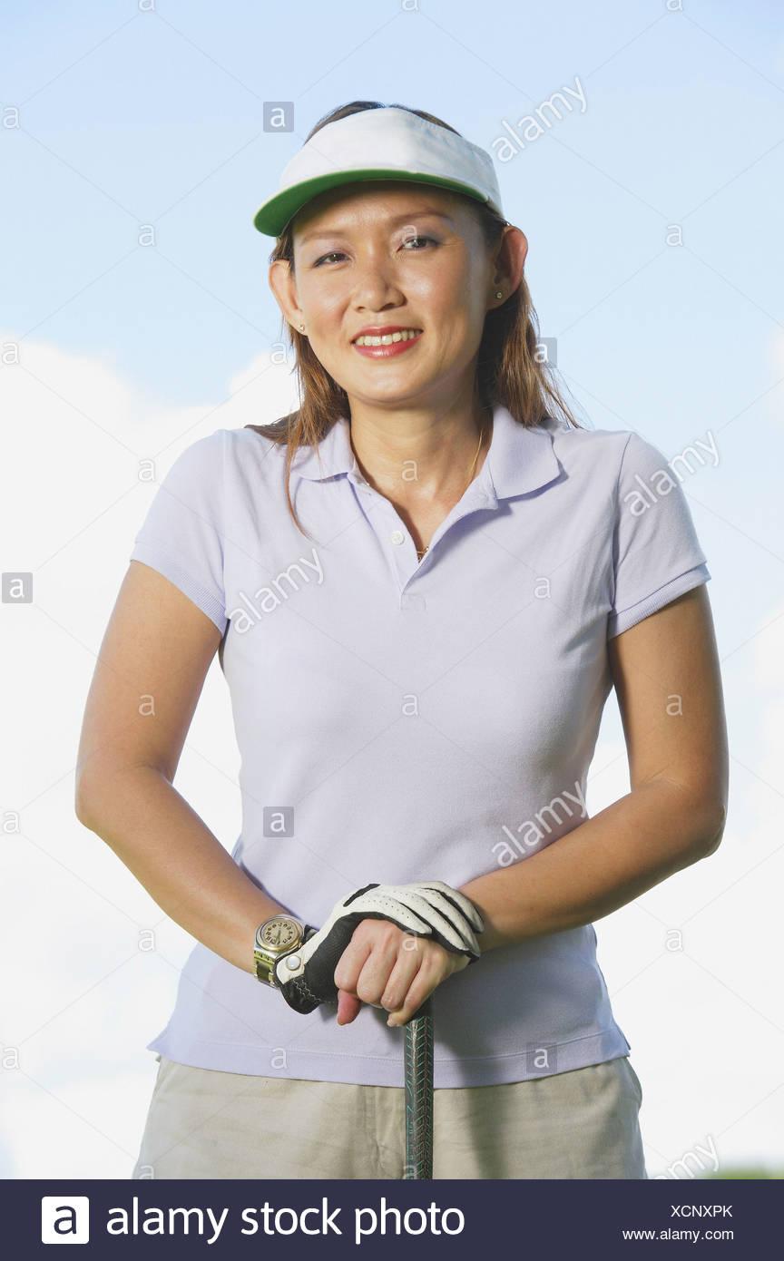 f055359f Woman wearing sun visor, leaning on golf club Stock Photo: 283223771 ...