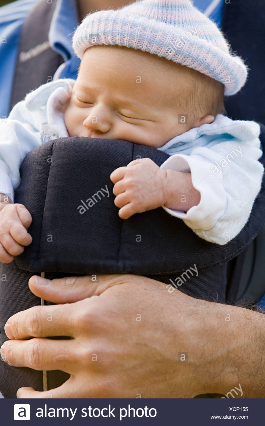 A father carrying his baby in a baby carrier - Stock Image