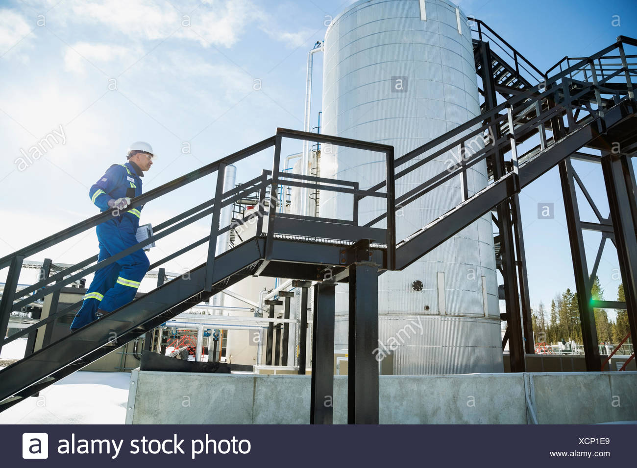 Male worker ascending platform stairs at gas plant - Stock Image