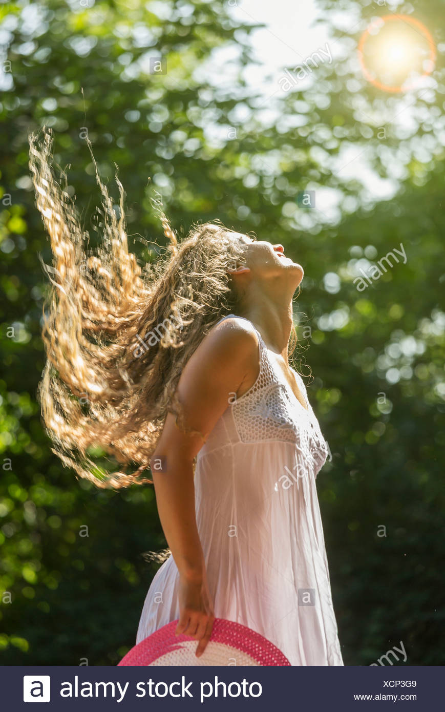 Teenage girl wearing white sundress tossing long hair, Prague, Czech Republic - Stock Image