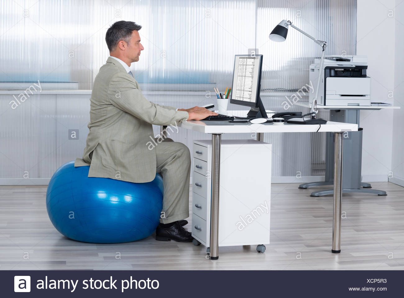 Businessman Using Computer While Sitting On Exercise Ball - Stock Image