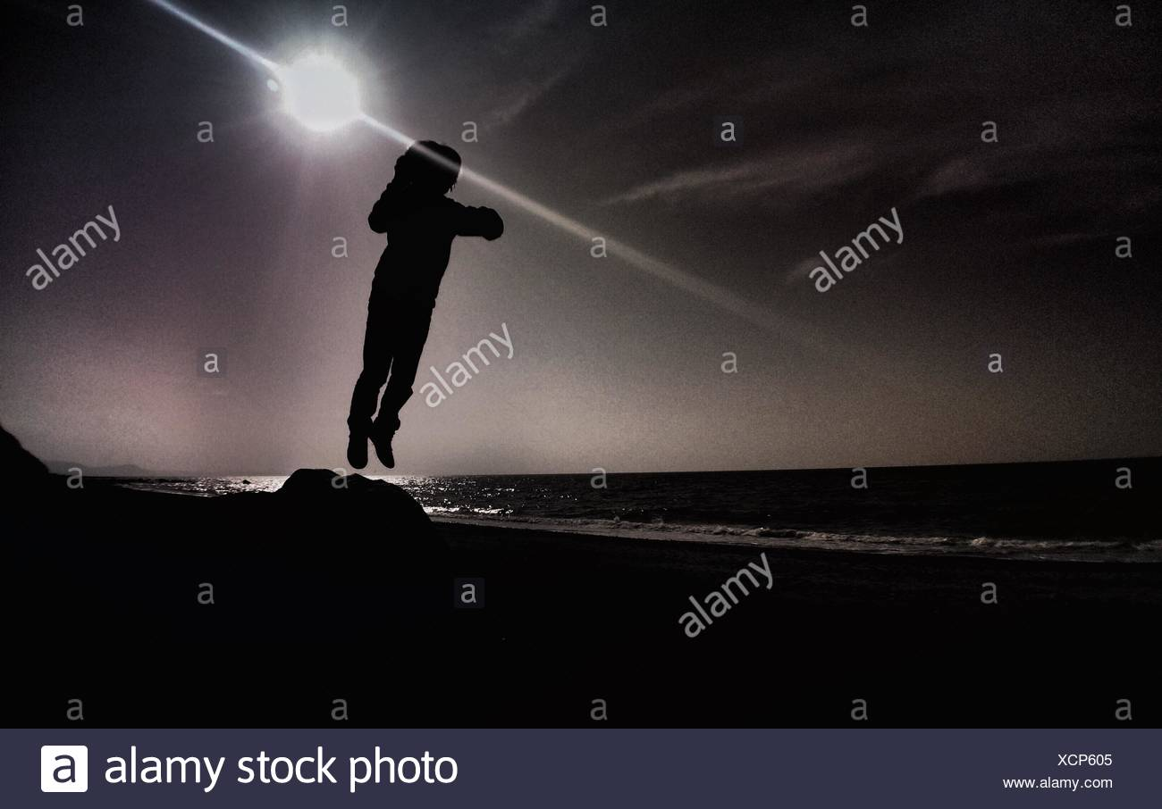 Person Leaping Into Air Against Sun Stock Photo