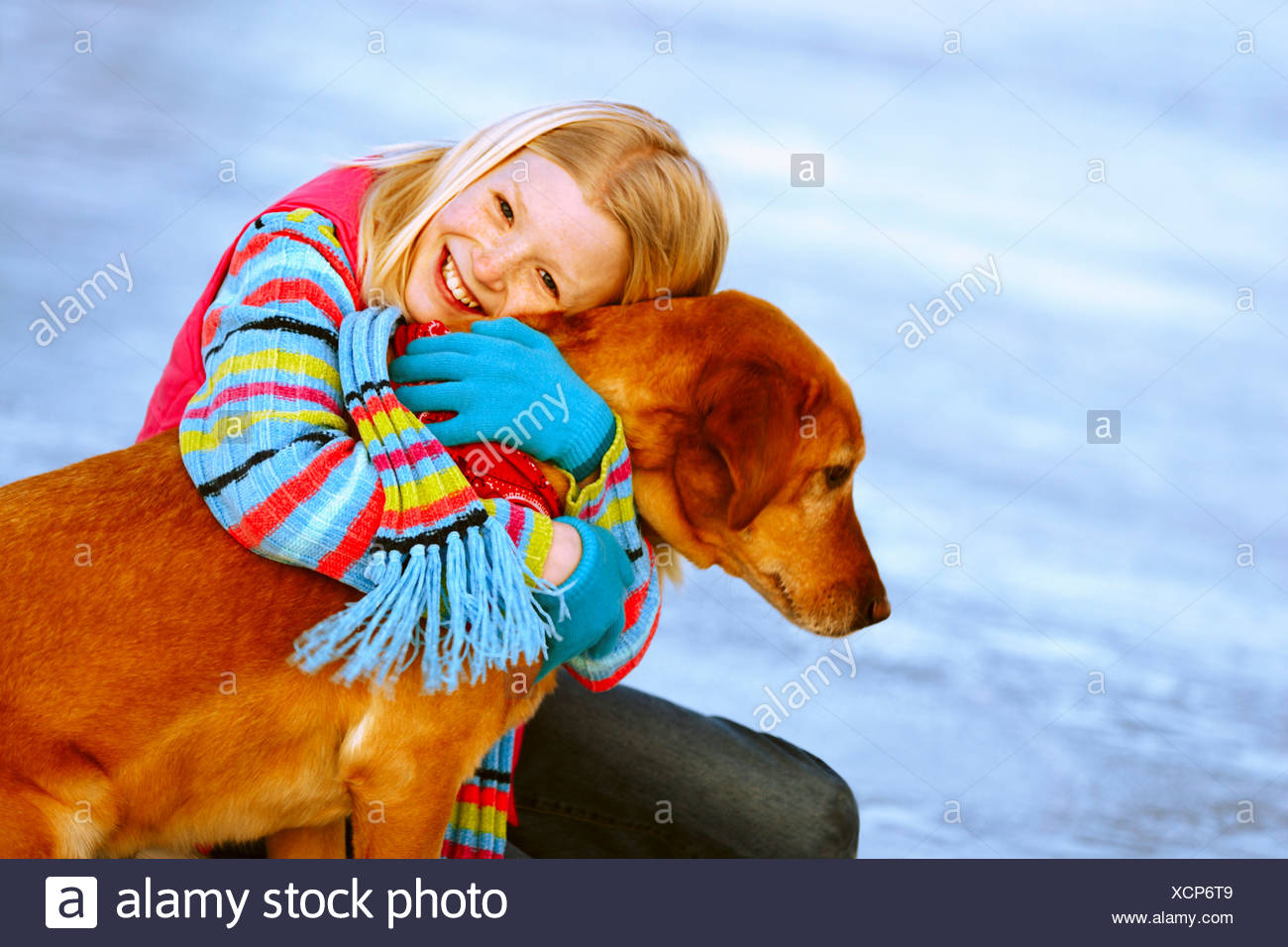 Young girl embracing her dog - Stock Image
